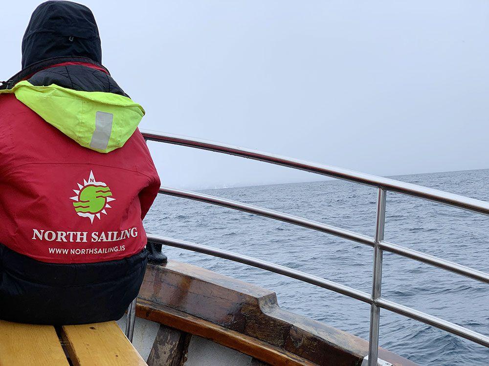 Turista esperando en el barco a que las ballenas aparezcan