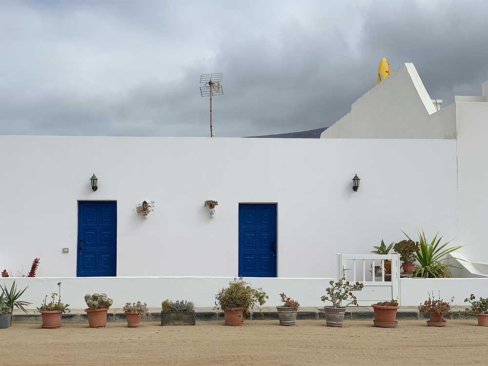 Fachada blanca con ventanas azules en Caleta de Sebo